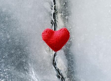 het heldere hete scharlaken hart dat van garen wordt gemaakt ligt op het duidelijke blauwe koude ijs en smolt de diepe barst