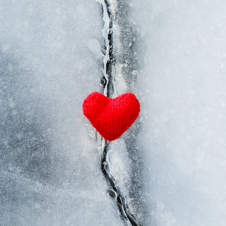 bright hot scarlet heart made of yarn lies on the clear blue cold ice and melted the deep crack