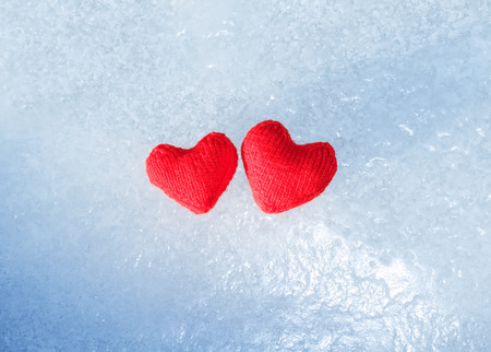 two bright red hot heart made of yarn lying on the cold transparent blue ice