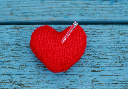transparent sharp cold icicle impaled warm knitted heart on blue wooden table