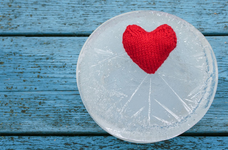 the warm red heart lies surrounded by the sharp cold of ice on a blue table Stockfoto