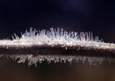 takplanten bedekt met scherpe glimmende transparante ijsvorst tegen de blauwe winterochtend Stockfoto