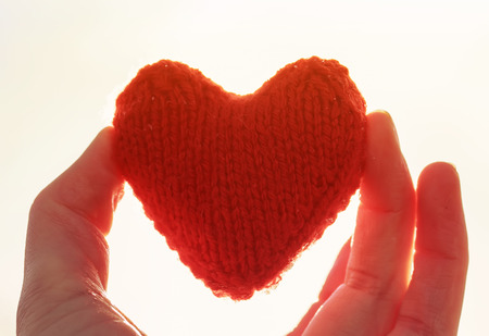 red knitted heart keeping my fingers on the background of Sunny yellow bright colors