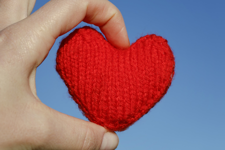 red knitted heart lies in the warm fingers of the hand on blue sky background
