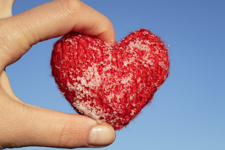 red knitted heart is covered with cold ice crystals lies in the warm fingers on blue sky background