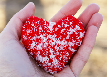 warm knitted red heart is covered with cold ice crystals lies in the palm of your hand Stockfoto