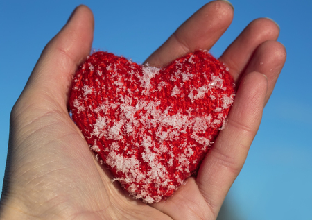 red knitted heart is covered with cold ice crystals lies in the warm hands