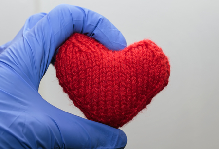 warm knitted red heart holding a hand in medical gloves