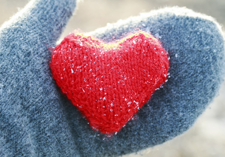 warm knitted red heart is covered with cold ice crystals rests in the palm in the grey mittens