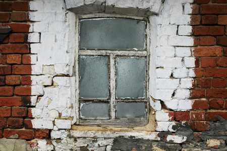 an old window with a rickety wooden frame in the brick wall of a village house