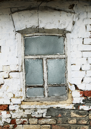 small old window with glass in frost with a rickety wooden frame in the brick wall of a village house