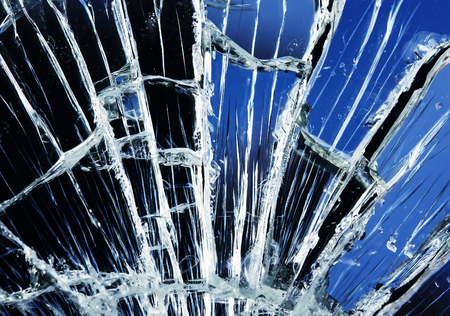textured background of a blue mirror covered with small and large white cracks and splinters