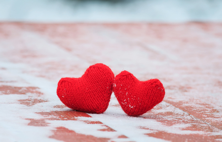 the symbol of love two red warm knitted hearts lie together on a wooden table under the snow