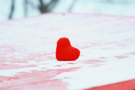 the symbol of love scarlet heart on a wooden table under the snow in the Park Standard-Bild