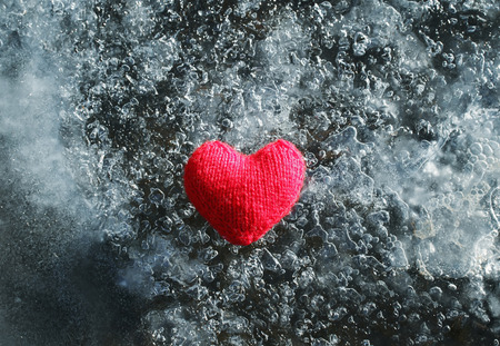 warm red knitted heart lying on the cold glittering ice