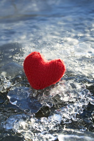 a symbol of love and warm holiday red knit heart on a sparkling cold ice Standard-Bild