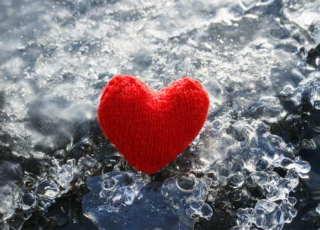 Warm red knitted heart lying on the cold glittering ice Standard-Bild