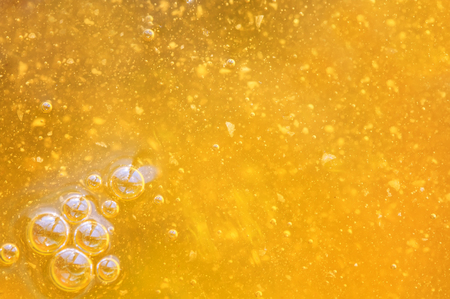 tasty liquid background of fresh Golden honey with bubbles glistening in the sun. Stockfoto