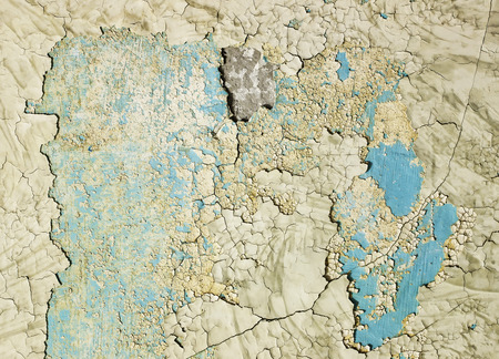 background of the texture of the old wall with many layers of peeling paint and plaster for repair