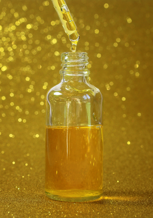 bright yellow beauty cosmetic oil stands in clear vial with dropper on shiny festive Golden background