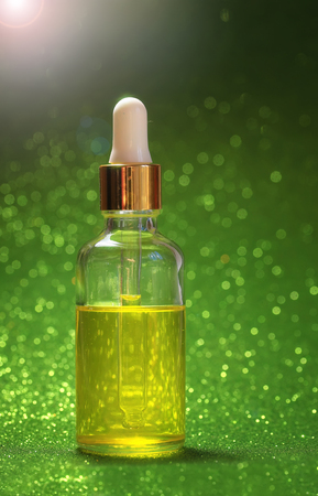 bright Golden cosmetic oil for beauty is in a transparent bottle with eye dropper brilliant green festive background Sunny