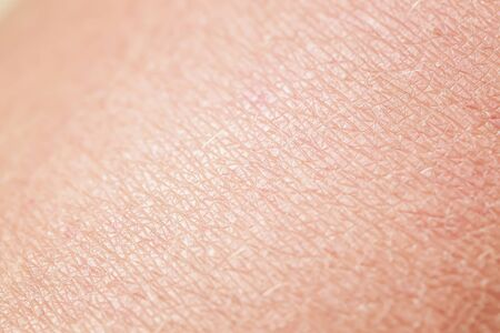 background of texture pink human skin covered with fine wrinkles and cracks
