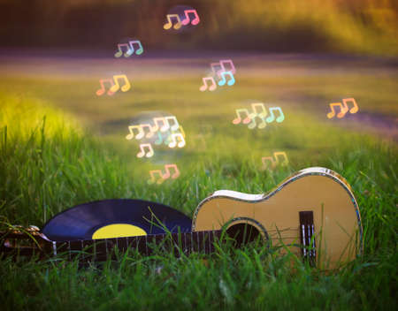background with music a wooden guitar and a vinyl record lie in the green grass and shiny notes sounds fly over it