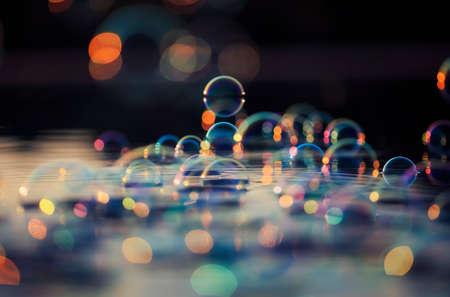 fabulous colorful background with shiny soap bubbles flying over the water and reflected in the sunset rays Standard-Bild