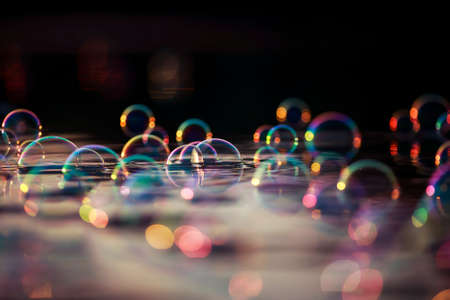 colorful background with shiny soap bubbles fly over the water and are reflected in the rays of the sunset