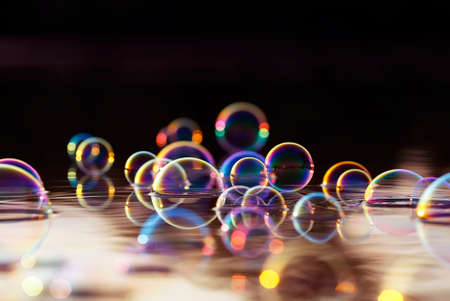 beautiful colorful background with shiny soap bubbles flying over the water and reflected in the rays of the sunset