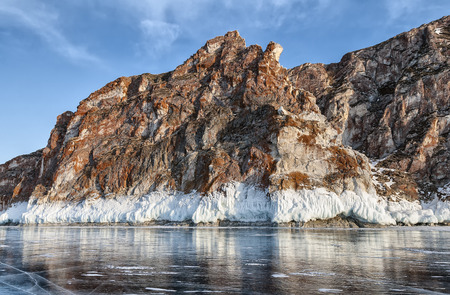 red cliff, bordered by white ice on lake Baikal
