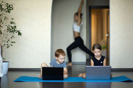 At home, two young children, a boy and a girl of 3-4 years old, work on a computer, her mother does yoga and stays calm. Activity.