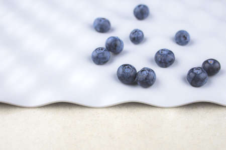 blue blueberries are scattered in a chaotic order on a gray background with space for text, close-up, blur.