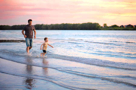 dad runs after his son along the riverbank at sunset. Stockfoto