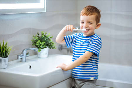 little boy brushing teeth in bathroom.