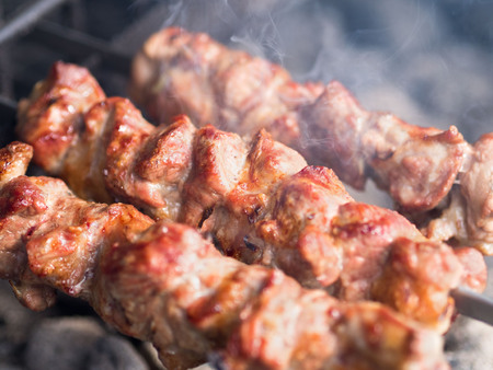 Grilled skewers of meat on the coals, with smoke. The street food.