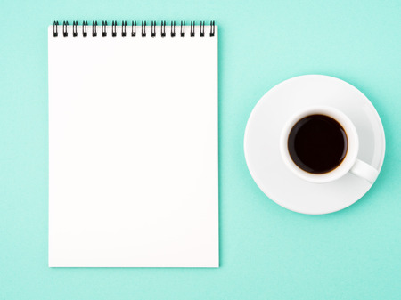 Notepad open with white blank page for writing idea or to-do list, a Cup of coffee  on bright blue background Stock Photo