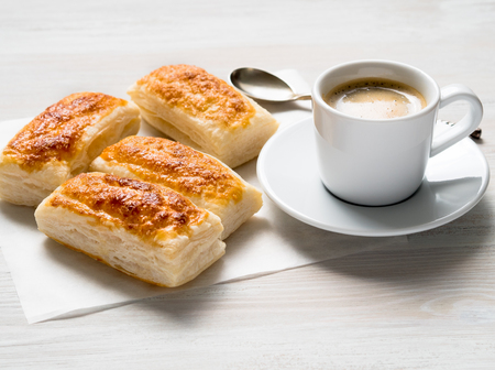 白い木製のテーブルにパフペーストリーとコーヒーのカップの新鮮なロールと朝の朝食。側面図、日の光。 写真素材