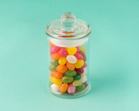 glass jar with sweets, candy on a turquoise background.
