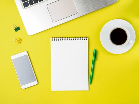 Top view of modern bright yellow office desktop with blank notepad, computer, smartphone. Mock up, empty space