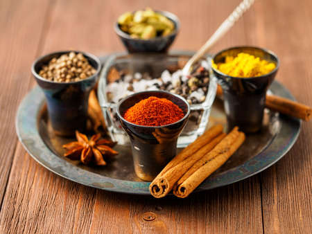 Oriental spice set - coriander, red pepper, turmeric, cinnamon, star anise, rosemary various seasonings in metall cups, on brown wooden table, side view, mcro, selective focus. Stock Photo