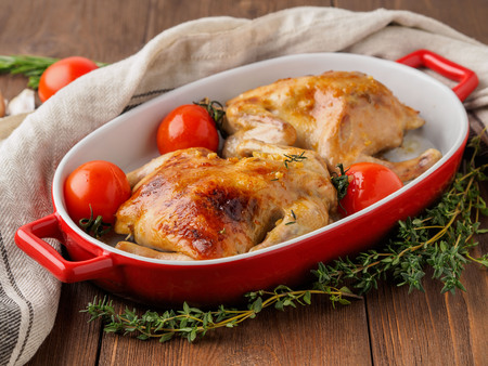 two carcasses fried chicken in a bowl, baked chucks in an oven with tomatoes, with crispy crust on dark brown wooden rustic table, side view Stock Photo