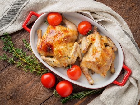 two carcasses fried chicken in a bowl, baked chucks in an oven with tomatoes, with crispy crust, on  dark brown wooden rustic table, top view Stock Photo