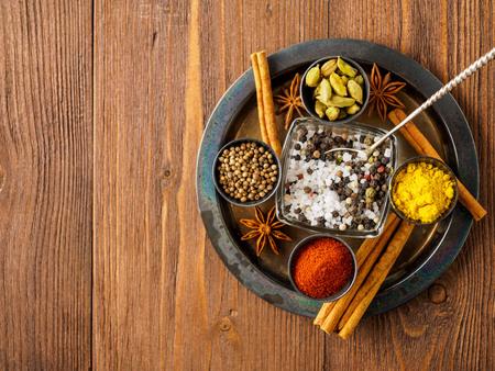 Oriental spice set - coriander, red pepper, turmeric, cinnamon, star anise, various seasonings in metall cups, on brown dark wooden table, top view, macro, empty space. Stock Photo