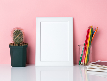 Blank white frame, crayon in jar, plant cactus  on a white table against the pink wall with copy space