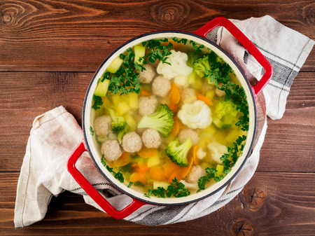 large metal cast red pan with delicious hot soup of vegetables and meatballs, cauliflower, broccoli, carrots, peppers, potatoes, healthy diet food, top view, wooden background Stockfoto