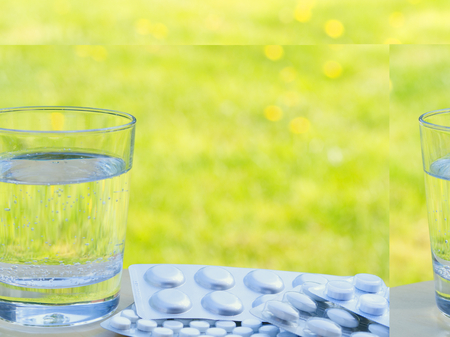 A glass of water and a pack of pills on the table on green background with grass, nature, bright sun. Allergic to flowers and pollen. Empty space for text.