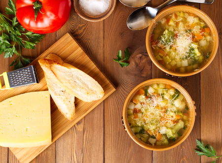Two bowl of minestrone soup with cheese on a cutting board and vegetables on rustic wooden background, top view.