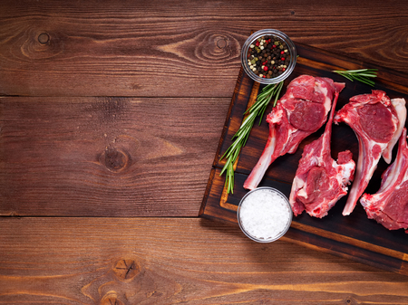 Raw lamb cutlets on bone on dark brown wooden background, lamb ribs, top view, copy space. Archivio Fotografico - 103258676