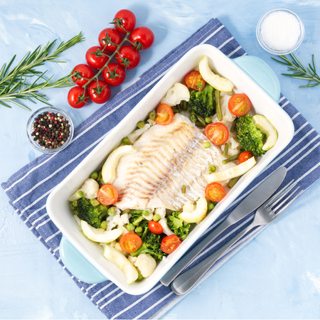 Fish cod baked in blue oven with vegetables - broccoli, tomatoes. Healthy and diet food. Blue stone background, top view.
